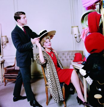 Stephen Jones/The young Halston places a hat on the head of actress Anita Colby at Bergdorf Goodman department store. New York 1965_Photo Ormond Gigli